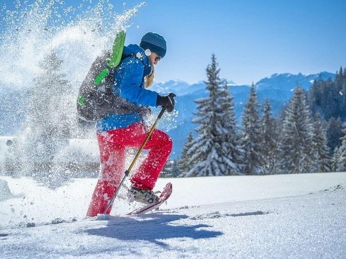 Frau beim Schneeschuhwandern mit der BOB in den Bergen