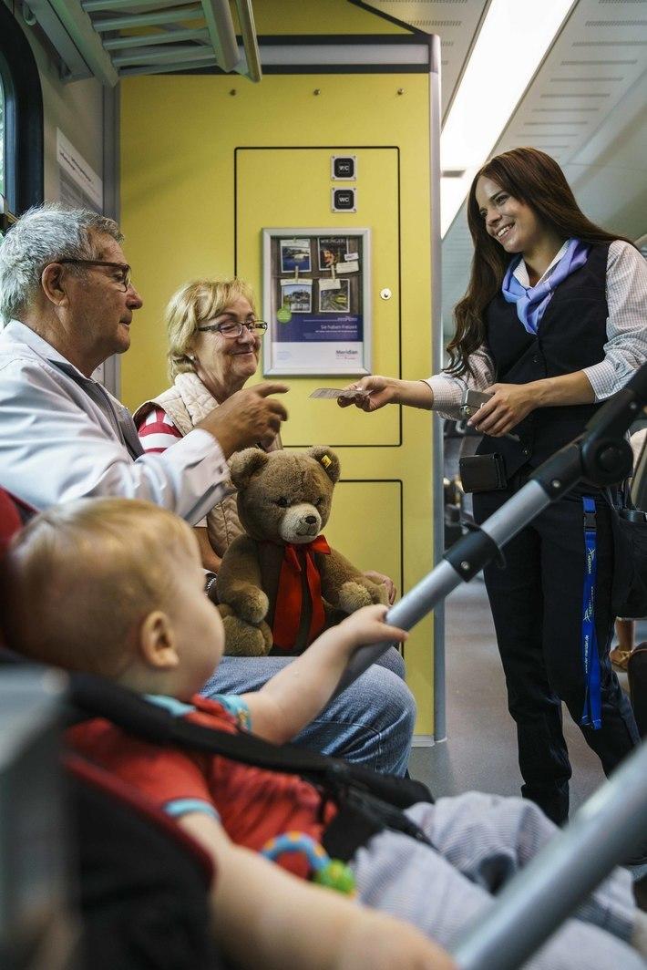 Kundenbetreuerin mit Fahrgästen im Zug