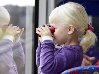 Kind schaut mit Fernglas aus dem Bus
