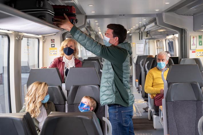 Zugbegleiterin hilft einer jungen Frau beim Verstauen eines Koffers