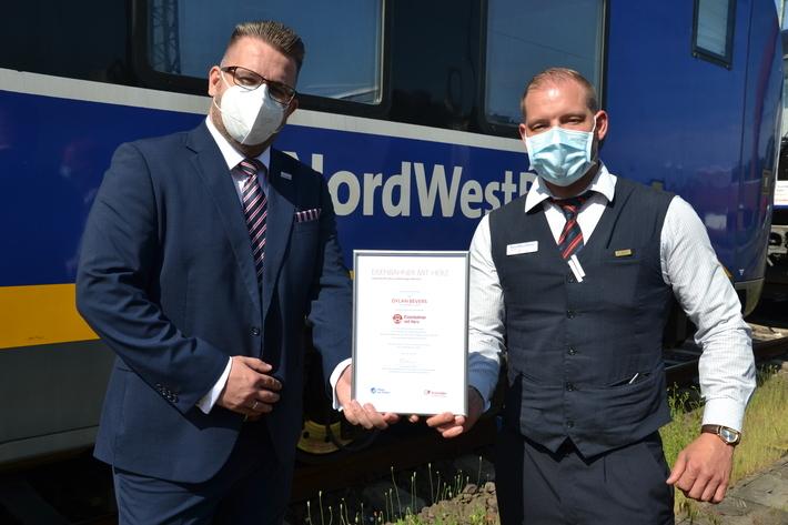 Dylan Bevers bekommt die Auszeichnung für den Landessieg von Robert Palm, Regionalleiter der Regio-S-Bahn Bremen/Niedersachsen und des Weser-Ems-Netzes, überreicht.