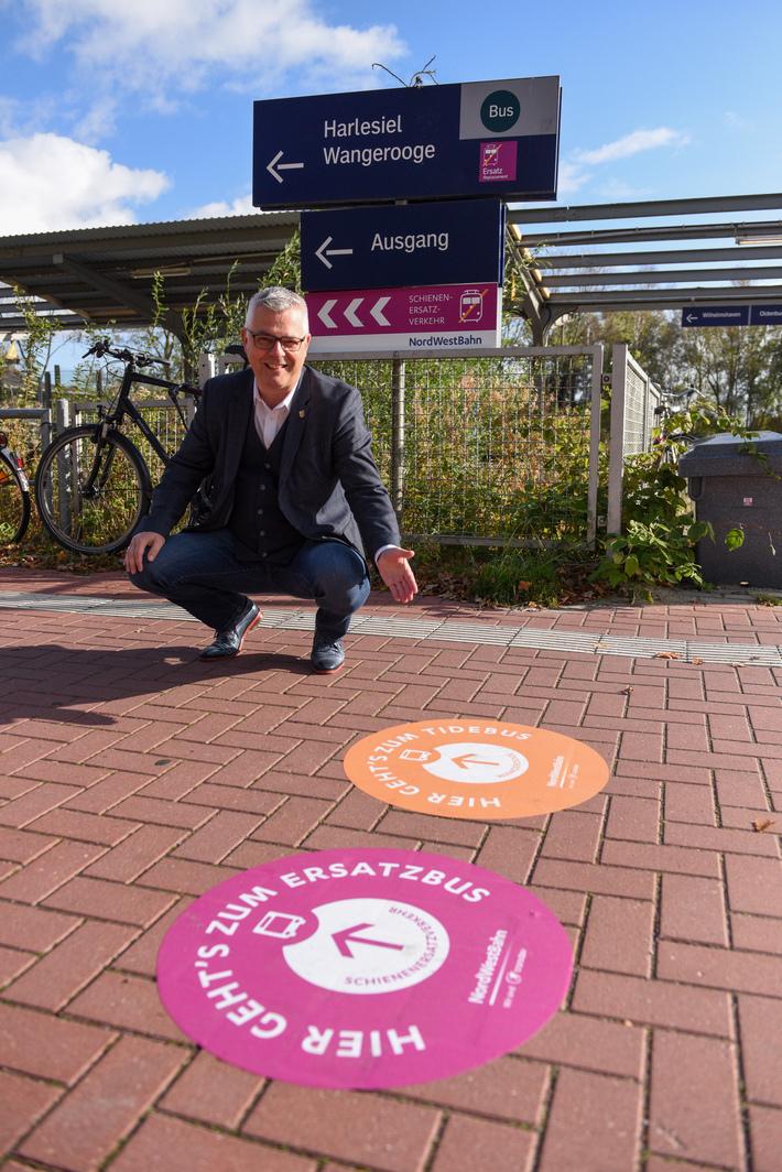 Sandes Bürgermeister Stephan Eiklenborg zeigt sich erfreut über das neue Wegeleitsystem der NordWestBahn am Bahnhof Sande. Foto: NordWestBahn/Elisabeth Schomaker