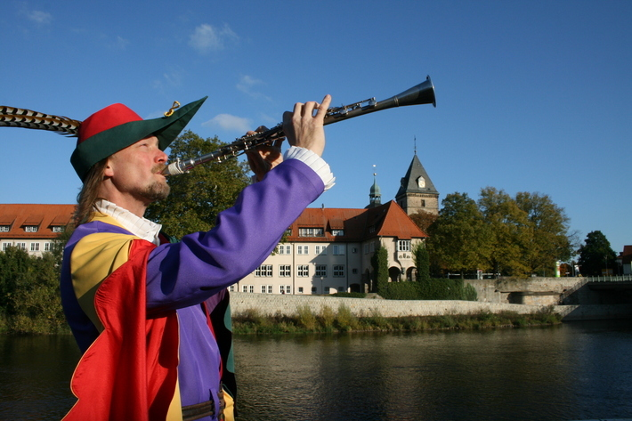 Der Rattenfänger spielt eine Flöte. Weser im Hintergrund.