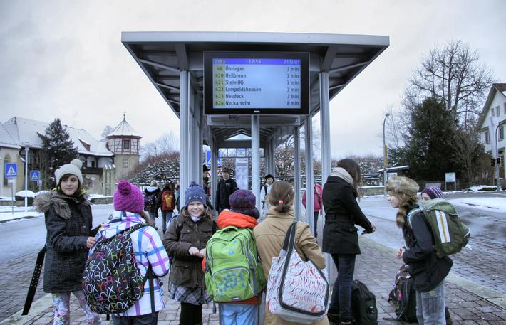 Kinder an Bushaltestelle mit Abfahrtsmonitor