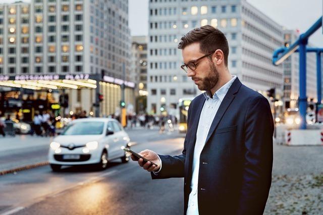 Ein junger Mann steht auf einem belebten Platz und blickt auf sein Handy