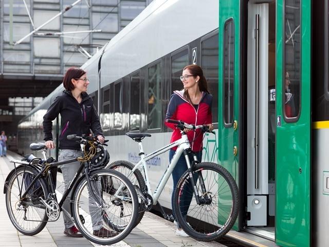 zwei Personen steigen mit Ihren Fahrrädern in einen Zug