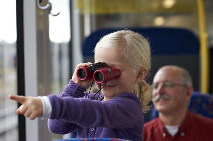 Kind mit Fernglas im Zug